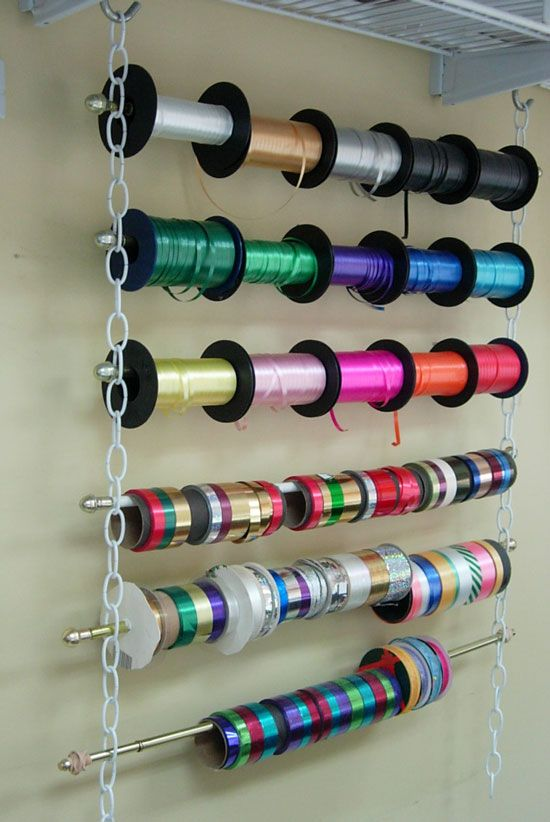 Great idea for ribbon storage ~ No drilling, sawing or painting required. All you need is 2 equal lengths of chain, Cafe style curtain rods and 2- S Hooks (2 eye hooks to screw into a ceiling or wood shelf if you don't have wire grid shelving shown in the photo)