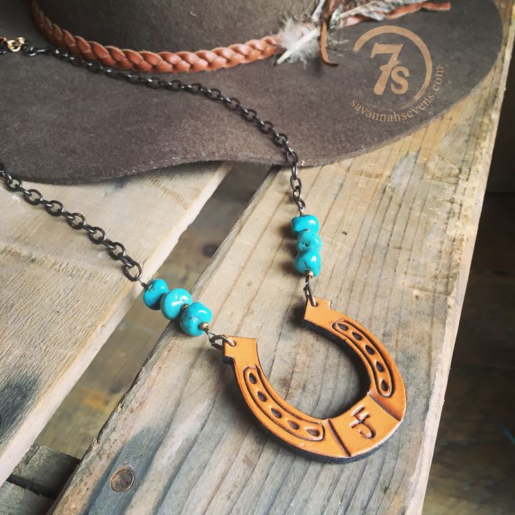 """- Leather horseshoe necklace - Handstamped leather - Natural turquoise stones - Bronze link chain - Clasp closure - Lightweight - 23"""" long, 2"""" wide horseshoe - Handcrafted by JForks - Shown paired wit"""