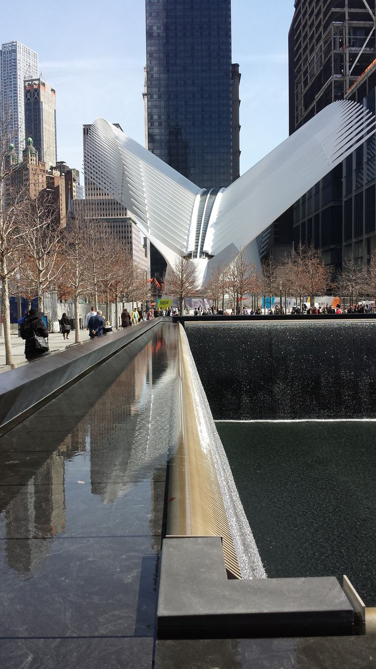 Part of the WTC 9/11 Memorial Fountain is in the foreground and the Oculus transportation hub is in the distance.