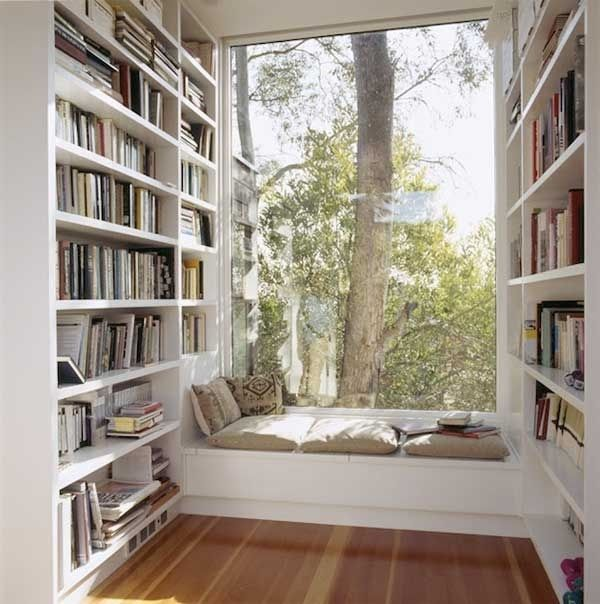 window seat with white bookshelves looking at tree