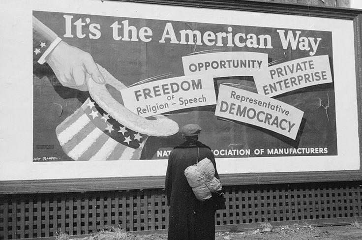 Migrant man looking up at billboard. Iowa. April 1940.
