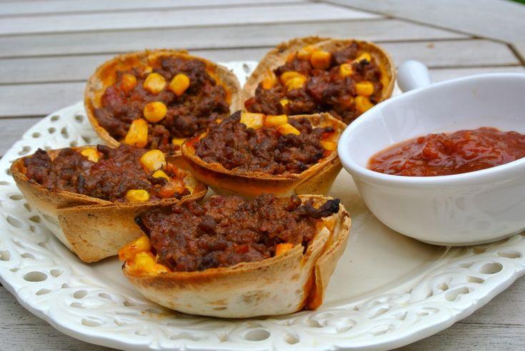 Weer een lekker Mexicaans recept: kleine tortillabakjes met een vulling van gehakt, tacokruiden, tomatensalsa en maïs.  Het is echt een heerlijk recept en het ziet er ook nog eens heel feestelijk uit!    Tijd: 15-20 min. + ongeveer 15 min. in de oven  Recept voor 12 Mexicaanse hapjes  Benodigdheden:    300 gram mager rundergehakt  150 gram salsa (saus in fles)  1 zakje taco kruidenmix  100 gram mais uit blik  50 ml water  4-5 wraps
