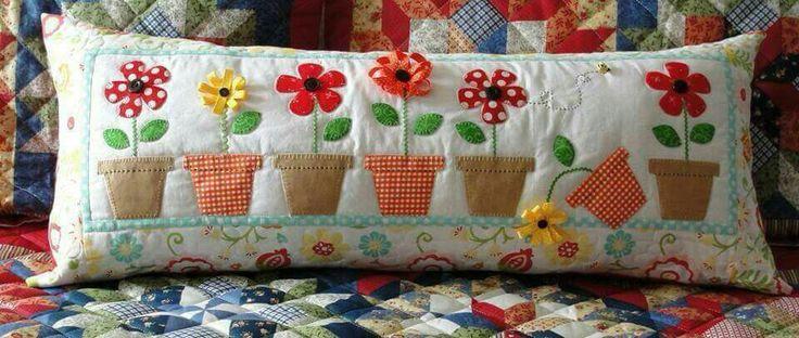 Cojín con aplicación de tiestos con flores de distintas telas. Patchwork.
