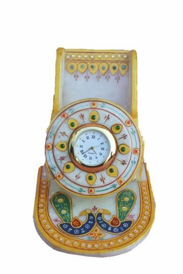 Enlighten your dwelling with this collection of antique decorative 'Marble Mobile Stand with Clock'. It is embellished with Meenakari and kundan work that is complemented by expert enamelwork.The marble mobile holder is perfect for all types of promotions and gift occasions .The beautiful embellishments made by carving stone add value to them.