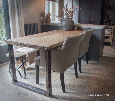 Stoere grof houten eettafel met metalen poot. Eromheen de eetkamerstoelen Le Bistro van Interiors DMF in gave kunstleer met dierenhuidprint, en aan de andere kant een oud bankje