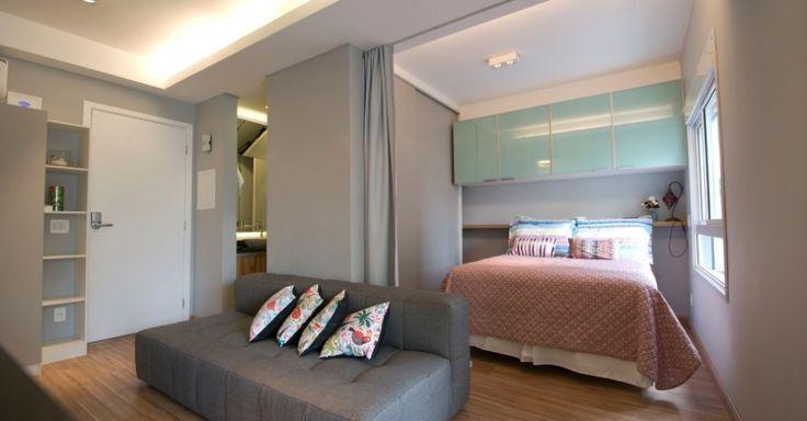 Integrado à sala de estar, o quarto possui um guarda-roupa cinza, com portas de correr  (à esq.), um armário verdinho de vidro temperado e uma prateleira em madeira que segue sobre a cama até o limite do fechamento corrediço. Neste cantinho, os proprietários armazenam o varal de chão, já que o imóvel não dispõe de área de serviço. O projeto de reforma do apê com 35 m² é do arquiteto Leandro Matsuda