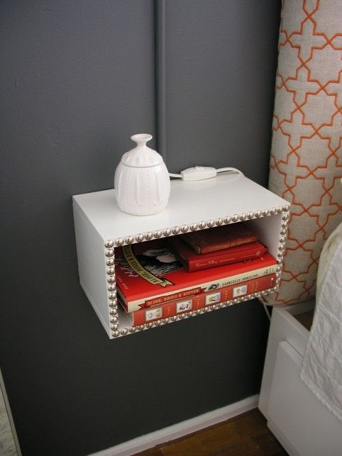 You'll need wood, 1″ L-brackets, wood glue, small finishing nails, screwdriver and a hammer. First, using a screwdriver make a box of the wood. Then paint it and decorate with finishing nails; fix it on the wall. You can also put a lamp above it on the wall. Such a night stand would be a perfect variant for your small bedroom and it's a comfortable storage space for your books or other things.