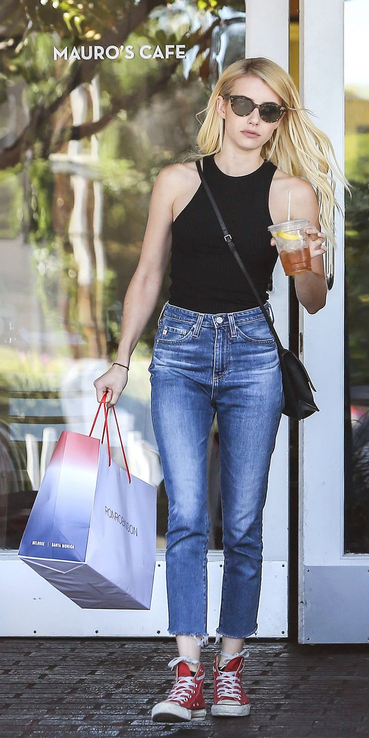 Emma Roberts has got the '90s look down pat—she went out for a coffee/tea run in a cutaway black top tucked into a pair of high-waist frayed jeans, complete with a cross-body bag and red Converse high-tops.