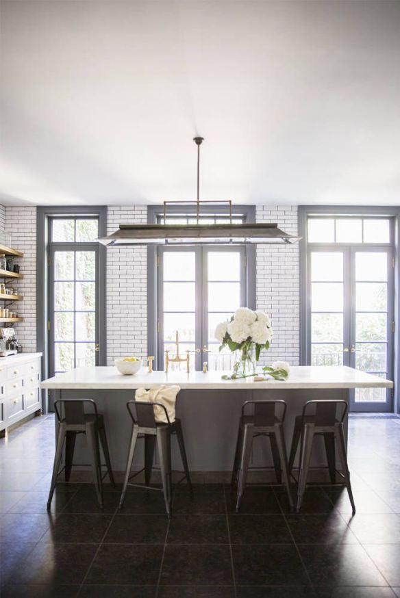 Domino Magazine Kitchen. White subway tile, dark grout, painted trim, gold fixtures