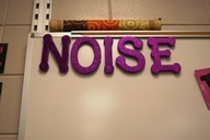 NOISE...remove one letter at a time when the voice level gets too loud. When NO is left, there is NO talking allowed. Period.