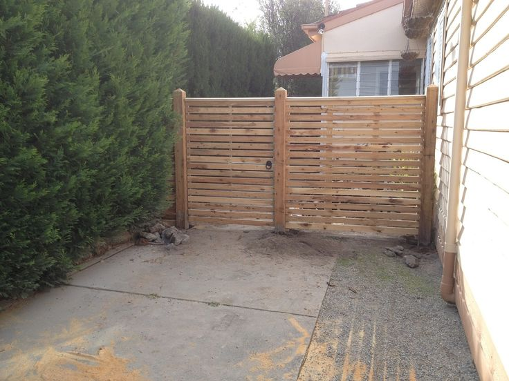 Horizontal side feature picket fence with exposed posts, points and capping with pedestrian gate. Styles of fences