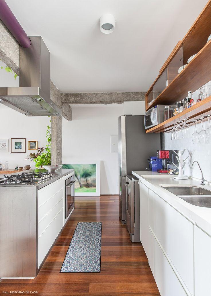 Cozinha integrada tem revestimento de subway tiles, marcenaria com portas de vidro e ilha com estrutura em aço.