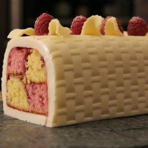 Battenburg cake iced with white icing and topped with raspberries and lemon slices.