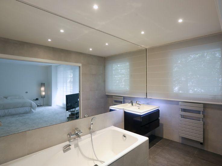 Un grand miroir, d'un seul tenant, recouvre le mur principal. La douche est en partie recouverte de mosaïques de marbre noires. Le carrelage est anthracite au sol (60x60cm) et gris au murs(30x60 cm). Très lumineuse, elle est ouverte vers l'extérieur grâce à une fenêtre et sur le reste de l'appartement via une porte double encastrée. Le meuble vasque, de fabrication Française, dispose d'un éclairage LED intégré - Xavier Lemoine Architecte d'Intérieur Paris 17-