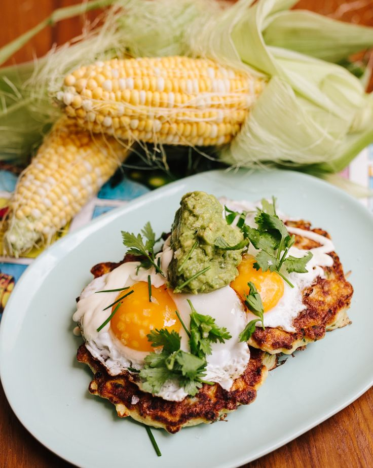 Sweetcorn fritters topped with guacamole, sunny side up egg & sour cream