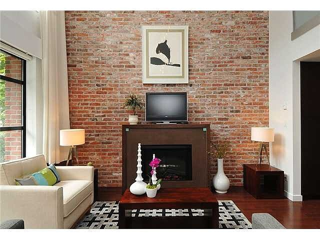 A Bricked Feature Wall Highlight The Fireplace In A Living