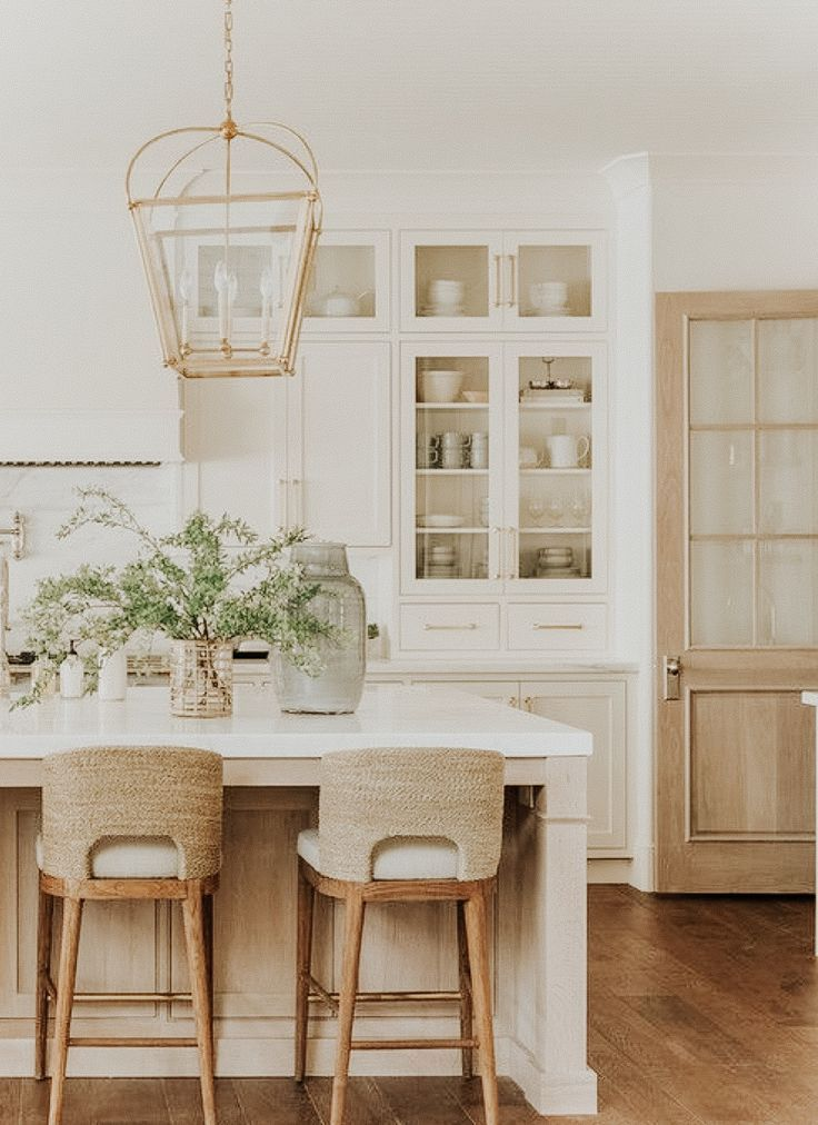Casual kitchen design in California with white kitchen cabinets and rattan bar stools, light wood kitchen cabinets and marble counter with gold-tone cabinets.