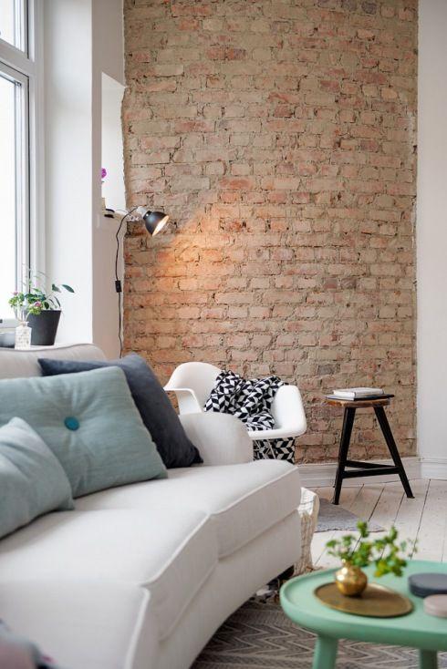 półokrągła ściana z czerwonej cegły TIK,biała sofa,turkusowe poduszki w stylu skandynawskim,czarny stołek z drewnianym blatem i nowoczesne białe krzesło na płozach