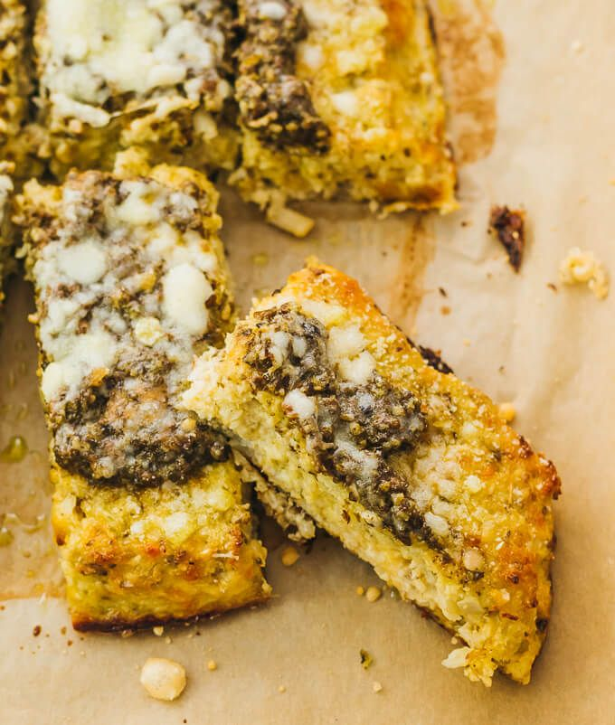 A Wedge Of Cauliflower Flatbread Topped With Pesto Sauce And