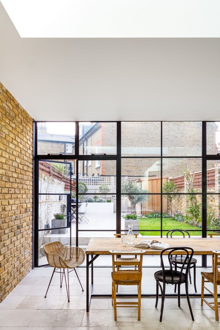 An amazing handleless shaker kitchen in a room with Crittal doors and exposed brickwork