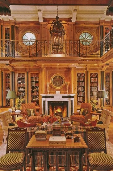 This is one of those rooms that take my breath away. All the architectural details, including the round windows, the beautiful warm wood and books, perfect sofas and chairs, etc. The railing around the loft is gorgeous.
