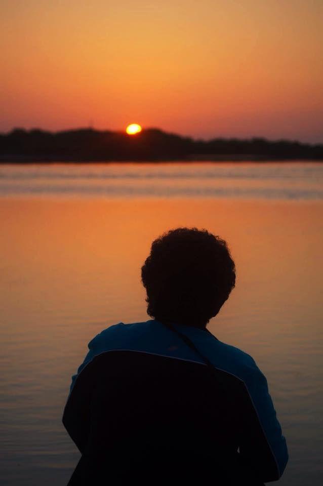 Contemplando el amacenecer; en esta imagen no se observa el rostro ya que se busca mostrar el efecto que da la subexposicion, la persona se sitúa frente a la fuente de luz y la cámara capta la silueta con efectos que encantan. Podemos apreciar en la imagen la ilusión de un amanecer, la paz y serenidad que provoca, lo relajante que es por unos instantes mirar los primeros rayos de sol; me  encanta los efectos que se suelen dar en las playas. foto tomada en Chelem, Yucatán.