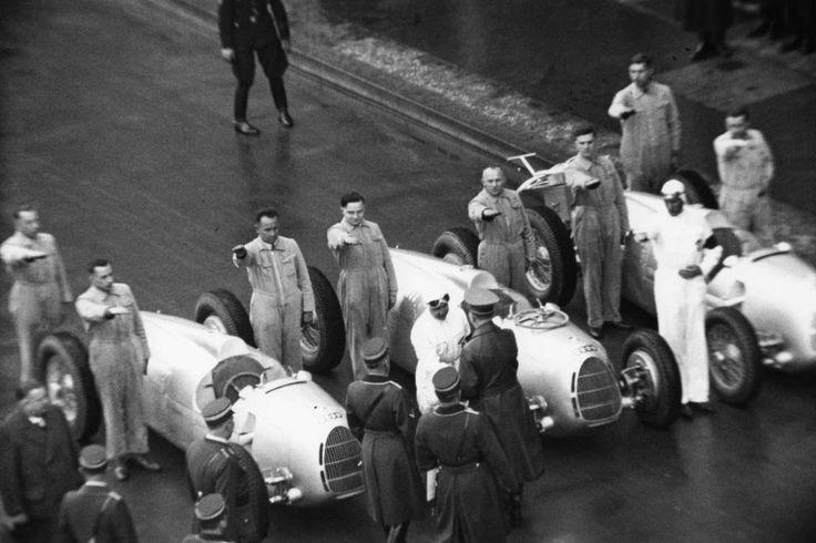 """Auch die """"Silberpfeile"""" und ihre Fahrer und Techniker machten den Hitlergruß: der """"Führer"""" und Angestellte der Auto Union bei der Eröffnung der Internationalen Automobil- und Motorrad-Ausstellung in Berlin 1937."""