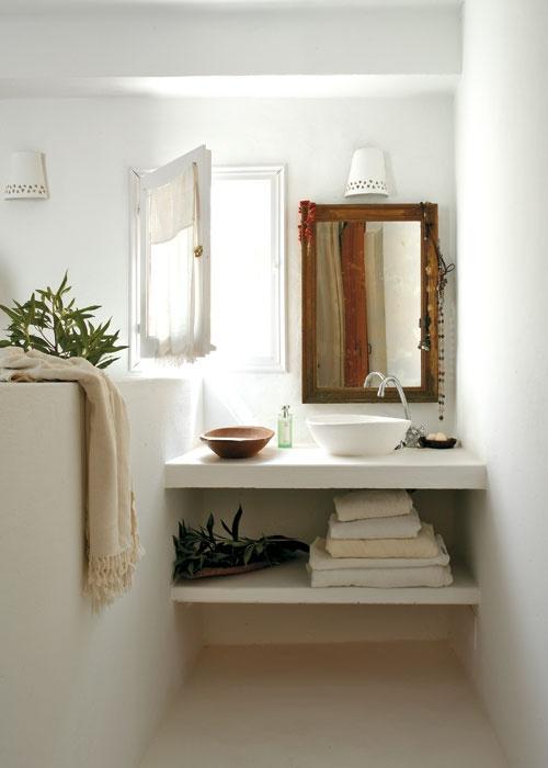 Qué buena idea. Tras es el cabecero de la cama hecho en obra, se ha aprovechado el pequeño espacio que quedaba para adaptar una zona de lavabo con encimera de obra, junto a la ventana. El blanco luminoso llena de magia el ambiente.