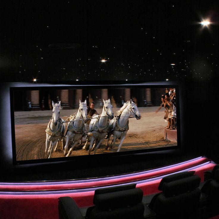 Salle de Cinéma Privée avec un écran au format cinémascope, équipé d'une toile trans-sonore compatible 4K de 380 cm. Le cadre est cintré et sa courbe est rétro éclairée pour la mettre en valeur.