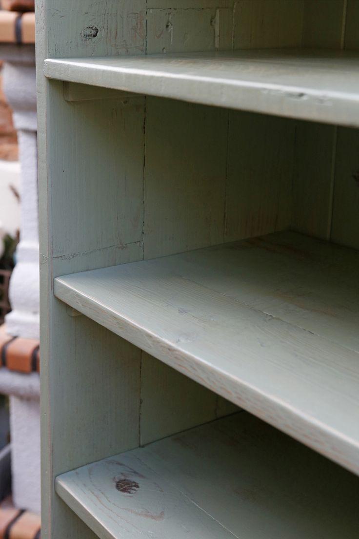Pormenor de armário para arrumação de sapatos, feito com madeiras reutilizadas e com pintura desgastada.