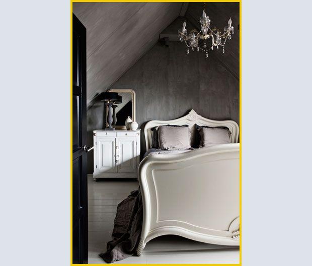 Tutto CURVE E VOLUTE, il grande letto bianco con cimasa di Goossëns. È un pezzo antico il LAMPADARIO A GOCC E