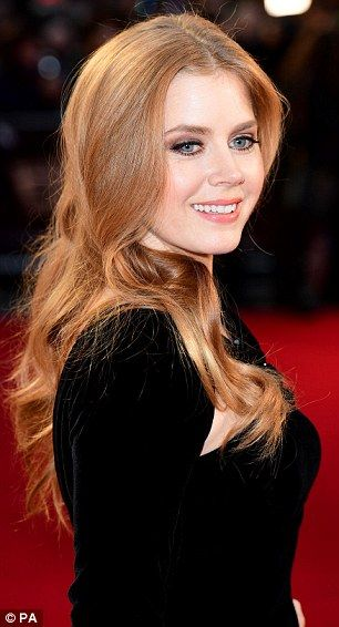 Chic: Her strawberry blonde hair was worn over her shoulders in loose curls and her face m...
