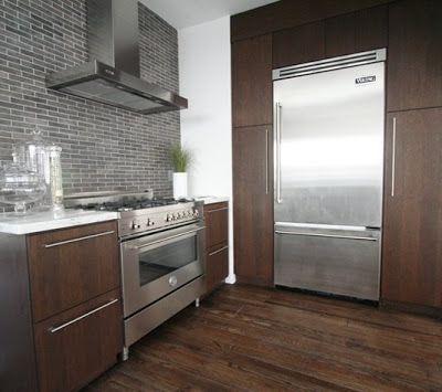 Cozinha gourmet com aparelhos de aço inox, armários manchados escuros, bancada de mármore e metálico pequeno tijolo telha cerâmica backsplash