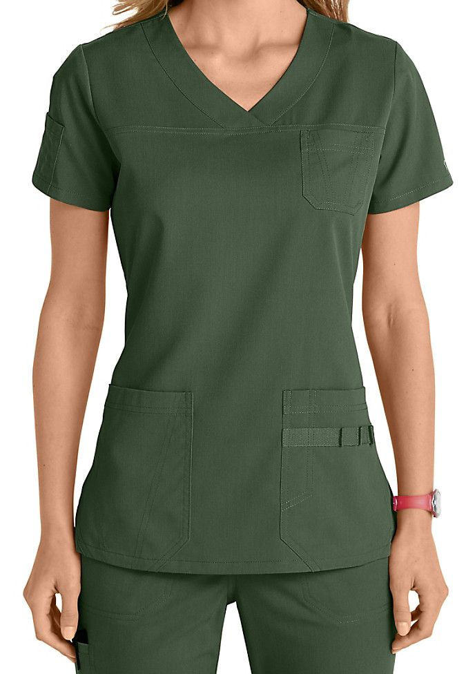 "Meet your new ""go-to"" top! This 3-pocket v-neck top from the popular NrG by Barco collection is loaded with cute accents including two patch pockets, a novelty sleeve pocket, a chest pocket, and pen slots."