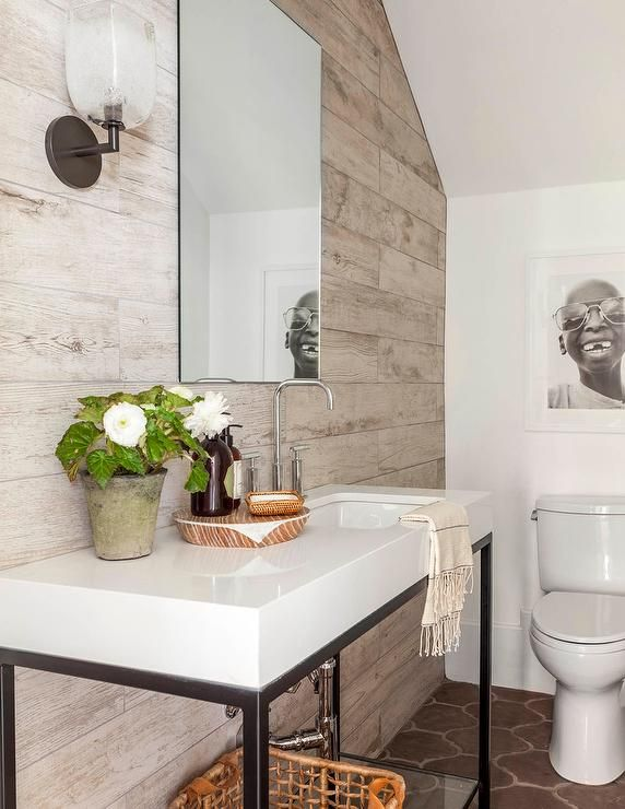 Modern cottage powder room features a plank accent wall lined with a metal washstand fitted with a thick white quartz countertop and a curved sink and high arc faucet placed under a frameless mirror alongside a Moroccan tiled floor.