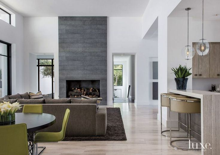 Grey slate fireplace with green chairs, wood floors, white walls and a breakfast bar.