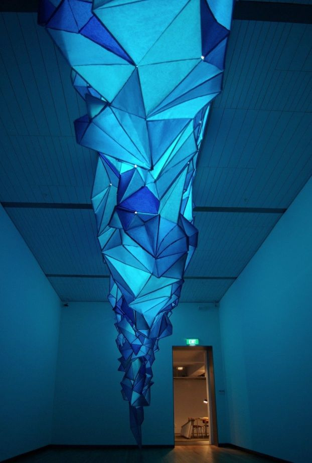 Gabby O'Connor made these beautiful icebergs hanging on the ceilings. This installation, What Lies Beneath, uses tissue paper and staples to construct these huge icebergs.