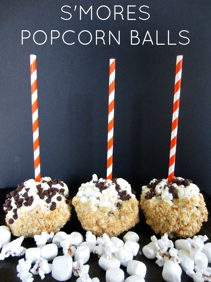 S'mores Popcorn Balls | Marshmallow popcorn balls dipped in white chocolate and sprinkled with graham crackers make an easy holiday treat! #smores #popcorn