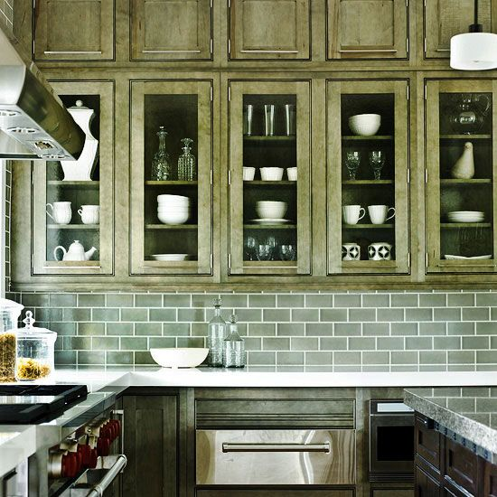 Dark cabinets can make a room feel smaller. Incorporating glass fronts onto the long, narrow cabinets in this kitchen helps the space feel lighter./