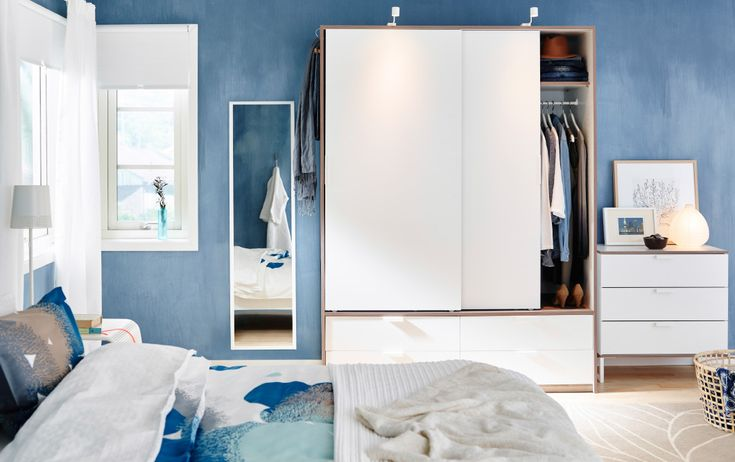 A bedroom with a large white wardrobe with two sliding doors and four drawers. Combined with a white chest of 3 drawers and a mirror.