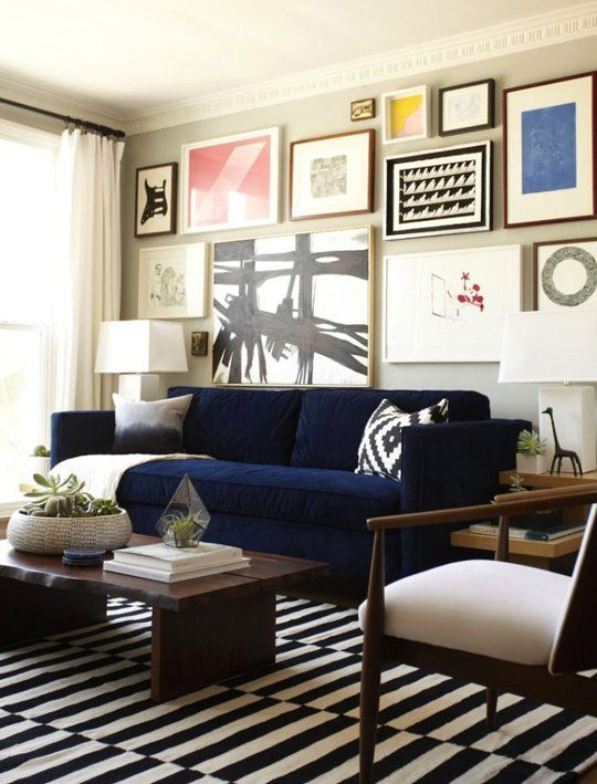 Orlando Soria's living room with a blue velvet sofa, black and white striped carpet and a gallery wall art installation.