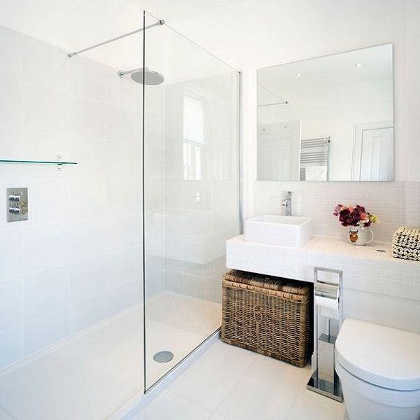 une petite salle de bain blanche aménagée avec une douche italienne étroite et ouverte.