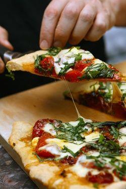 Pizza with fresh mozzarella, fresh tomatoes, and fresh basil.