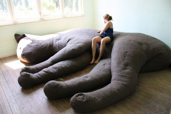 Very cool giant kitty couch, but my googling fingers are coming up short: anybody have any idea what plush master constructed this lovely sculpture? Update