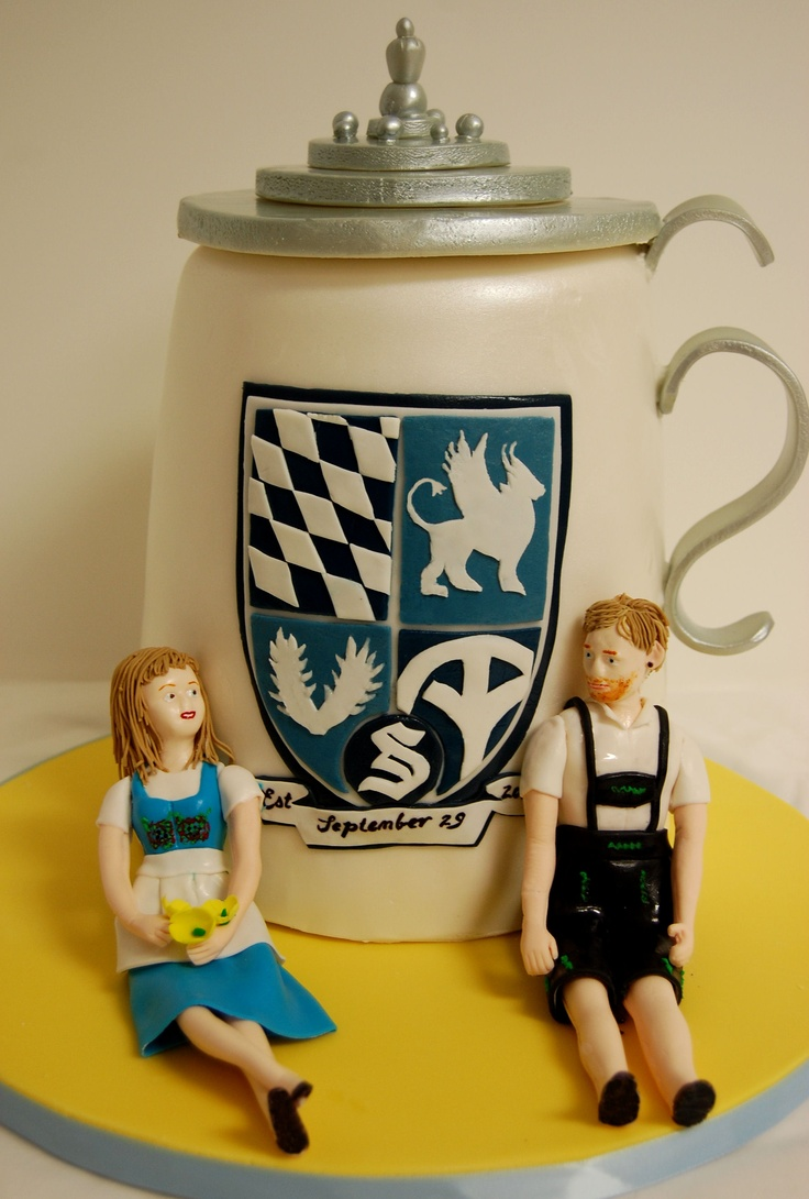 A beer stein cake featuring fondant figures made to look like the bride and groom in traditional German outfits.