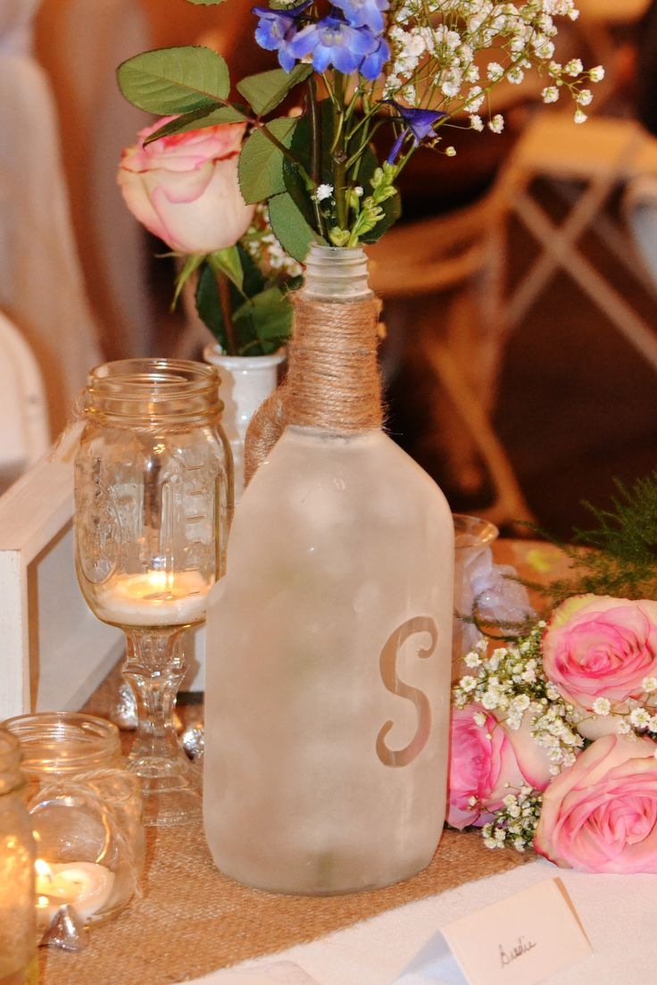 """another """"S"""" decoration. we frosted these old liquor bottles and stenciled out the S with some craft tape, added some twine and a few single stems."""