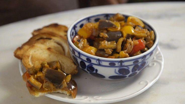 Receita com instruções em vídeo: Com uma mistura incrível de sabores, a caponata é uma receita maravilhosa para servir de entrada ou comer junto na refeição principal. Ingredientes: 4 colheres de sopa de azeite de oliva, 1 cebola em cubos, 1 dente de alho amassado, 2 berinjelas em cubos, 1 pimentão vermelho em cubos, 1 pimentão amarelo em cubos, 50g de azeitonas verdes fatiadas, 2 colheres de sopa de uva passa branca, 2 colheres de sopa de extrato de tomate, 2 colheres de sopa de vinagre de…