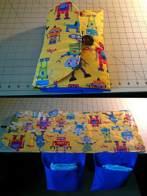 210/366: Travel diaper changing pad   - Based on this tutorial, this is the first of many sewing projects I plan to tackle for the baby. This is is a travel diaper changing pad with a layer of vinyl for waterproofing and pockets to hold wipes and diapers that folds into a cute little clutch.    Check back in a few months to find out how well it works!    Android camera