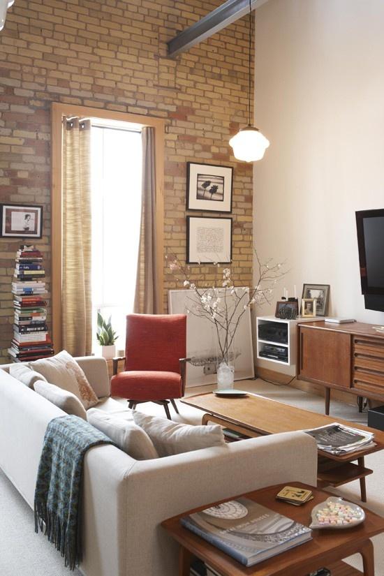 Salon vintage et contemporain avec son mur en briques.