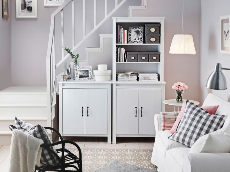 A bright living room with white cabinets, one low with doors and one high with doors and open storage at the top. Shown together with a white two-seat sofa filled with cushions in pink and white/grey check pattern.